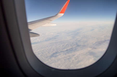 Looking through the plane window while flying on the wing and sky with clouds.