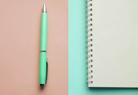 Spiral notebook with blank pages and fountain pen on pastel pink and mint background, top view, flat lay.