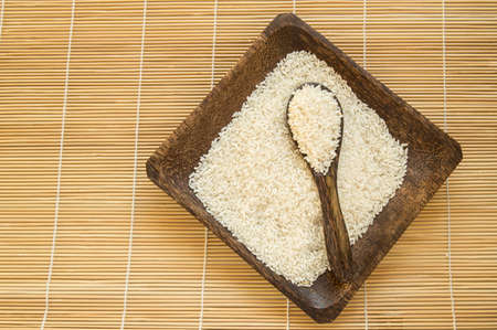 Raw white rice on wooden plate and wooden spoons with rice on bamboo napkin for healthy eating, vegetarianism, top view, flat lay. 版權商用圖片