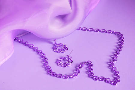 Purple silk, draped waves, silver chain and earrings, toned image in lilac, luxury accessories for women, background for jewelry and jewelry advertising.