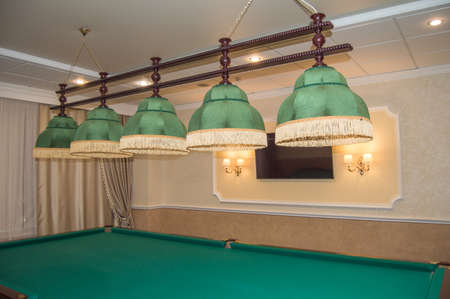 Luxurious interior of the living room with a billiard table and elegant green shades with lamps. Standard-Bild