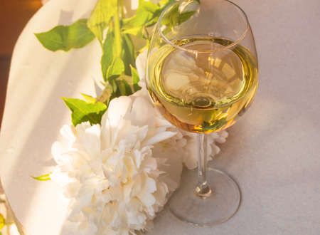 One glass of white wine and a white peony flower on a white table, top view. Relax with a glass of wine on a warm summer evening.