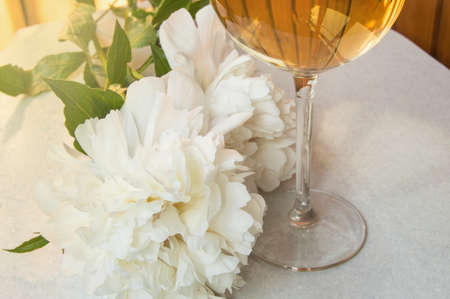 Still life, one glass of white wine, close-up stem of a wine glass, next to an elegant white peony flower. A lonely but joyful dinner after a days work.