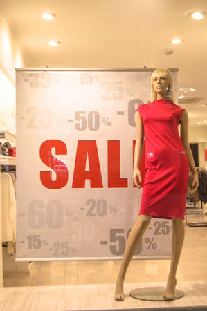 Shop window advertising the Final sale with a discount of 15, 20, 25, 50, 60 percent. Mannequin in a womens red dress on the background of a womens casual clothing store, vertical photo.