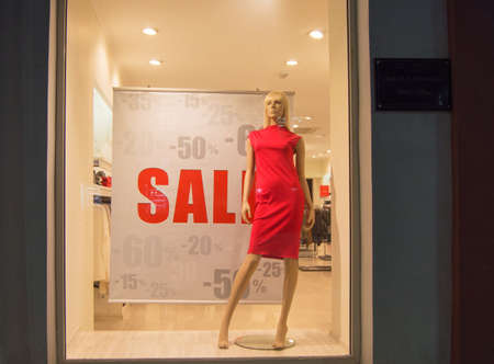 Shop window advertising the Final sale with a discount of 15, 20, 25, 50, 60 percent. Mannequin in a womens red dress on the background of a womens casual clothing store. Reklamní fotografie