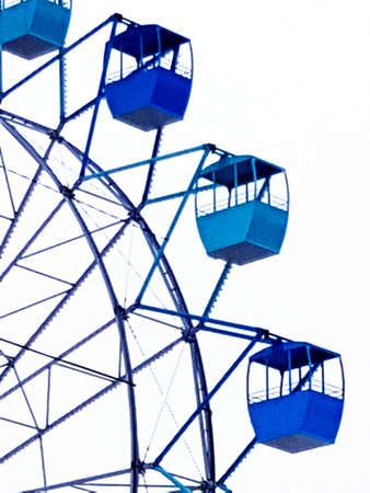 Close-up of the Ferris wheel, blue cabs against the sky, amusement Park.