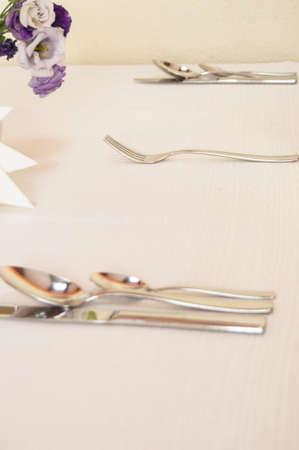 Close-up of elegant silver Cutlery on an empty, white set table, VERTICAL FRAME, serving waiting for guests.