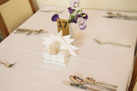 Close-up of elegant silver Cutlery on an empty, white set table, serving while waiting for guests.