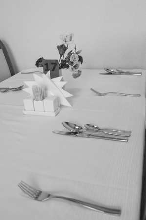 Close-up of elegant silver Cutlery on an empty, white set table, serving waiting for guests, vertical black-and-white frame.