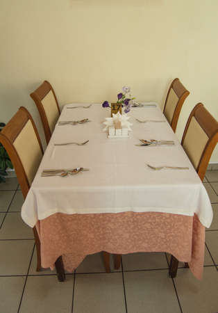 Festive table with tablecloth and Cutlery in the hotel restaurant waiting for guests, vertical shot, side view.
