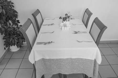 Festive table with tablecloth and Cutlery in the hotel restaurant waiting for guests, side view, black and white frame.
