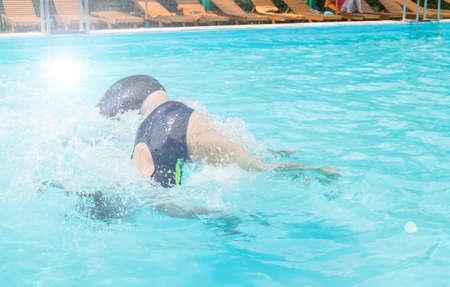 Due nuotatrici si tuffano contemporaneamente in una piscina all'aperto, dimostrando la loro abilità, Soleggiata giornata estiva, luce.