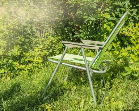 One empty folding garden chair for relaxing stands on the green grass on the lawn on a Sunny summer day, a copy of the space.