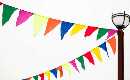 Festive triangular flags in the form of garlands hang tied to a lamppost. Decoration ideas in celebration of an event, isolated on a white background.