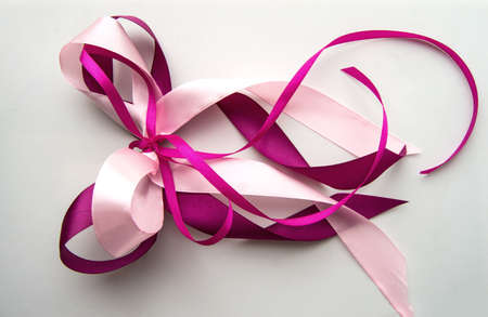 Pink and purple ribbon isolated on a white background, the concept of decorating gifts and postcards.
