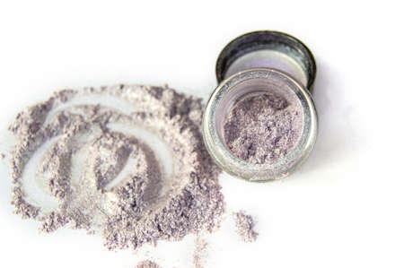 Scattered LILAC SHINY mother-of-pearl eye shadow on a white background, next to an open jar. 写真素材