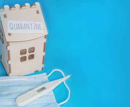 Medical mask, thermometer and wooden house and a piece of paper with the inscription QUARANTINE, the Concept of prevention of coronavirus disease.