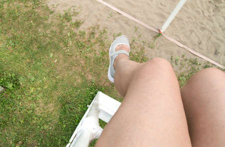 POV point of view of a woman sitting on a judge's chair on a beach volleyball court, a view of bare feet in sports shoes. Personal perspective of a girl looking down on grass and sand on a summer day.