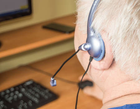 A gray-haired fat old man with a headset looks at the monitor screen, remote work, computer technology for pensioners, adaptation of disabled people to modern life. Фото со стока