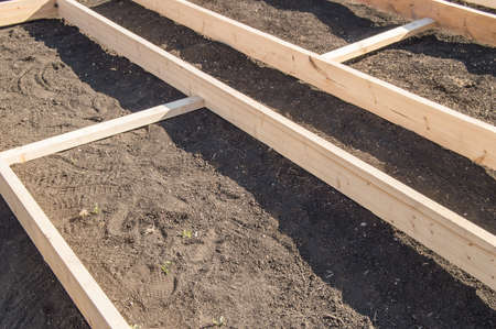 Wooden formwork from new boards for vegetable beds in the garden, preparation and construction, carpentry. Stock fotó
