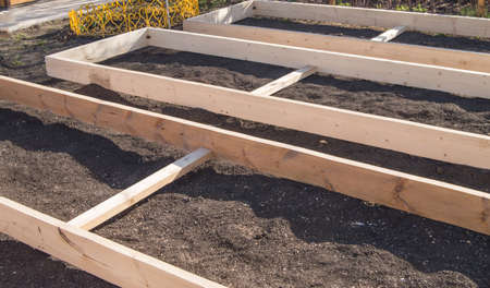 Wooden formwork from new boards for vegetable beds in the garden, preparation and construction, carpentry. Фото со стока