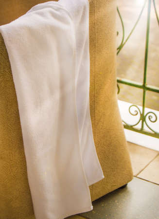 White Terry towel hanging on a chair, towel drying on the balcony, outdoor terrace against the background of sunlight, vertical shot