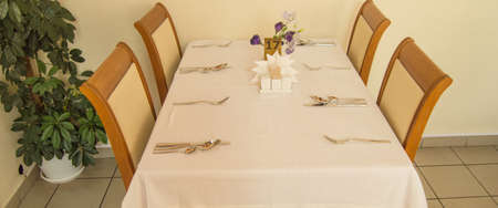 Festive table with tablecloth and Cutlery in the hotel restaurant waiting for guests, side view Reklamní fotografie