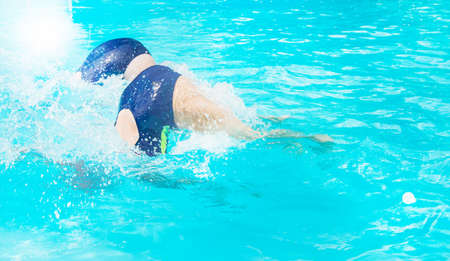 Two female swimmers simultaneously dive in an outdoor pool, demonstrating their skill, Sunny summer day, light