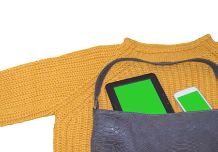 Women's yellow sweater and leather bag isolated on a white background, top view. The apartment lay with a mobile phone and a tablet with a green chrome screen and space for text. Copy space.