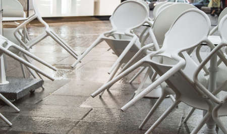 Wet white plastic chairs with raindrops in a street cafe, overturned, after a rain in Italy, in the evening.