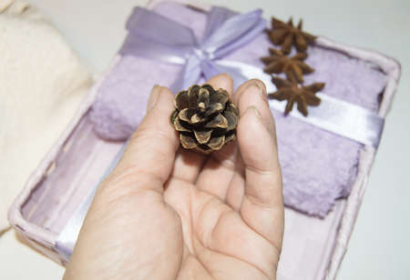 A woman's hand adorns a Christmas gift with Golden cones, packs Terry towels, and prepares for the holiday.