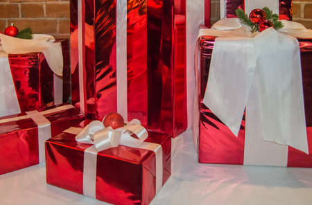 Christmas gift boxes wrapped in red foil and tied with white ribbon with decoration.