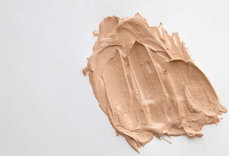 Nude tonal base smeared on a white background, texture. Фото со стока