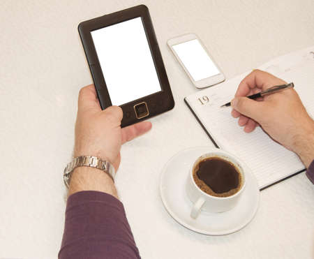Close-up with brutal male hands, writes interesting business ideas, planning and strategies in a diary while sitting at a table with a Cup of coffee, a modern smartphone and an e-book.