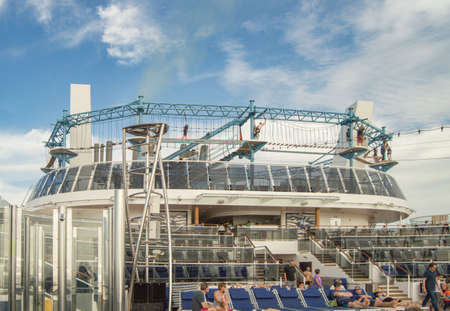 Mediterranean sea, Cruise ship MSC Meraviglia - October 10, 2018: Outdoor deck with swimming pool, sun beds, video screen, rope Park, vacationing tourists.