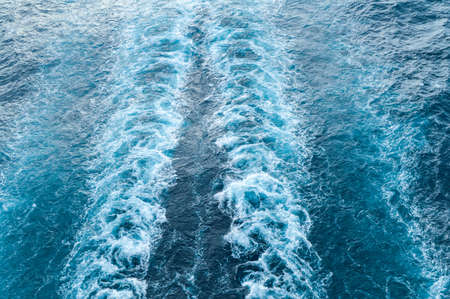 Stormy foam and a ship's track on the blue sea water. Фото со стока
