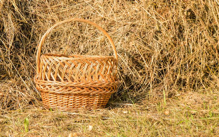 Wicker picnic basket and a haystack - a beautiful rural background in Sunny summer day