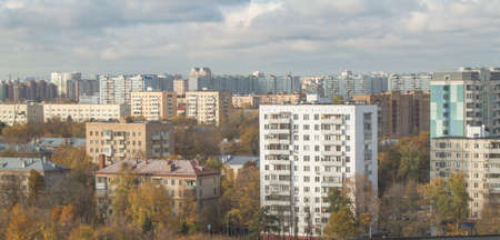 Autumn urban landscape - houses on the outskirts of Moscow at sunset, sky with clouds and residential buildings