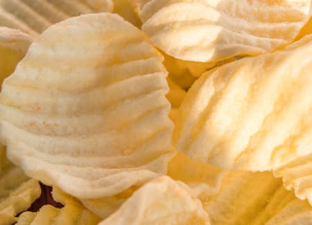 Yellow delicious salty potato chips in the background