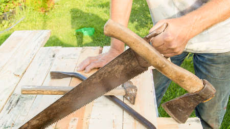 man uses a hacksaw, a hatchet, a claw hammer for construction work in your garden