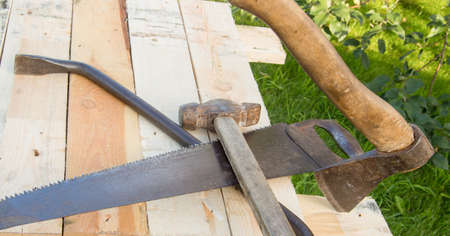building tools hammer, axe, hacksaw frame, lie on the light boards in the garden Фото со стока