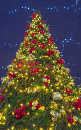 Richly decorated Christmas tree with colorful lights and sparkling balloons at night, outdoors, against a dark blue winter sky, bottom view, vertical. Фото со стока