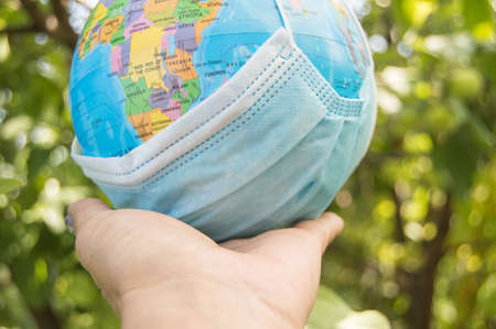 Hand holding a model of the globe in a medical mask, coronavirus control concept, outdoor, summer, blurred background of plants