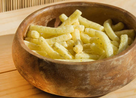 French fries in a wooden bowl, on a wooden background.