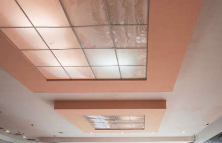 Pink ceiling with reflective tiles in a modern office space, conference room design