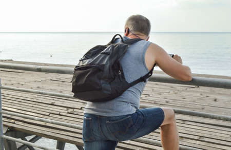 Man traveler with a backpack relaxing open sea, watching the dawn, leaning on the parapet, the concept of a lifestyle of freedom and relaxation
