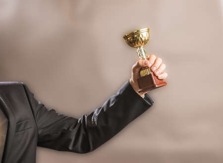 The businessman holds the champions gold trophy, the concept of success and victory