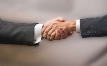 Close-up Handshake of two business partners in suits on a gray background