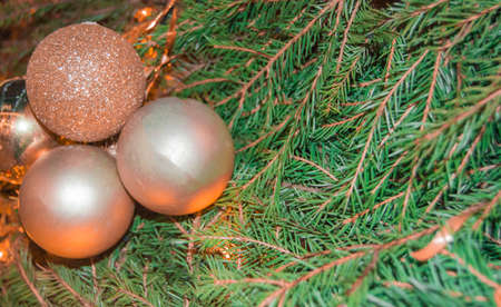 Gold shiny Christmas decorations. Glass balls on a real Christmas tree branch, new year background, banner