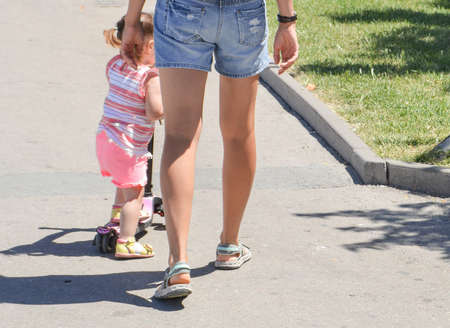 Young mother with bare legs, in shorts, walks with her little daughter in the Park, in the summer, outdoors. Фото со стока